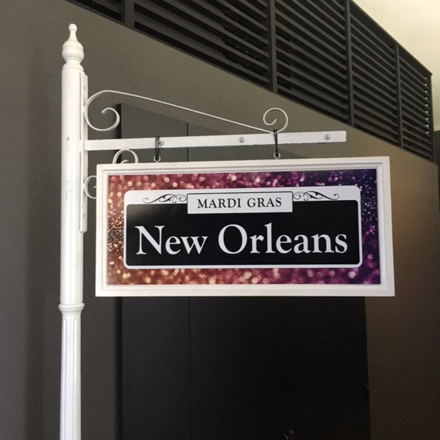 Large New Orleans Sign on White Sign Post